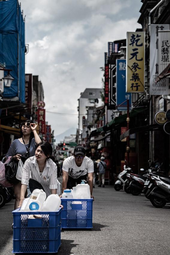 Woman and man walking while pushing box