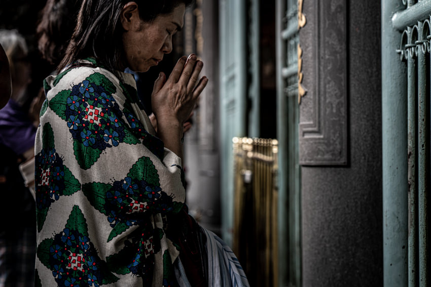 Woman praying seriously in Lungshan Temple