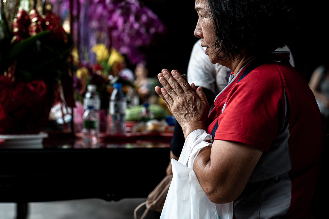 Woman praying seriously with plastic bag in Lungshan Temple