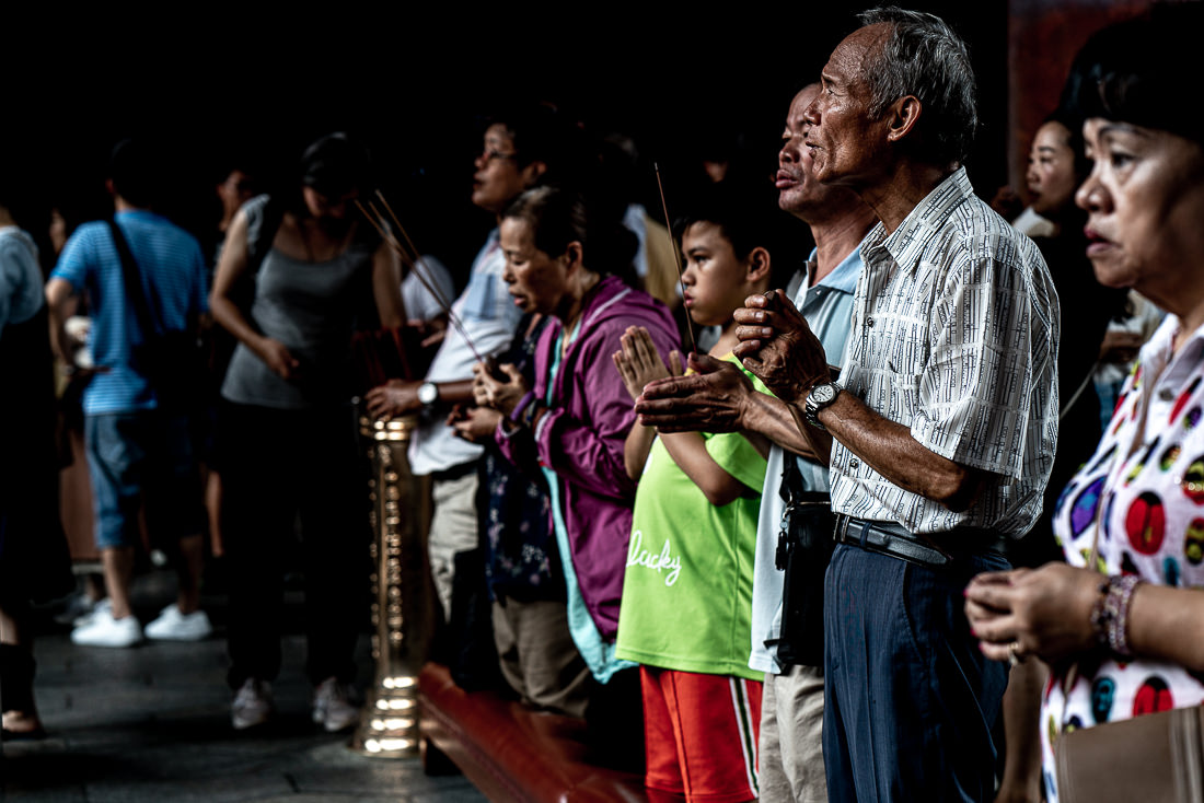 Young and old people praying in Lungshan Temple