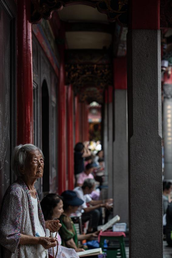 龍山寺の境内で数珠を手に立っていた老婆