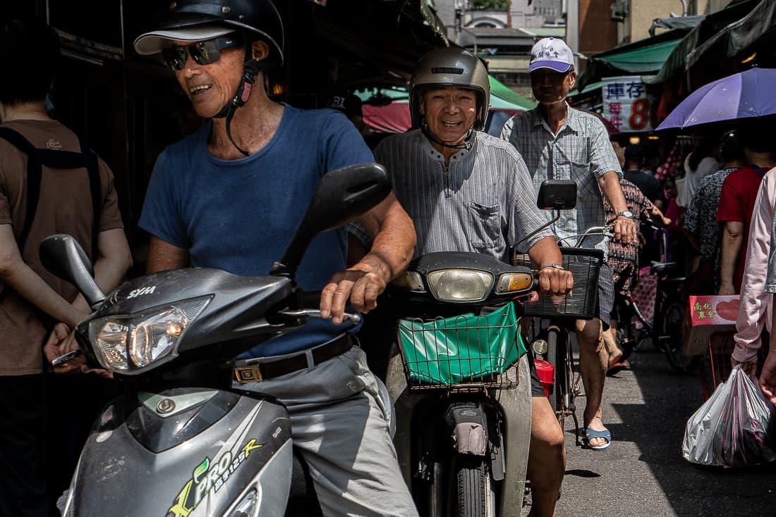 白蘭市場を走る二台のバイクと一台の自転車