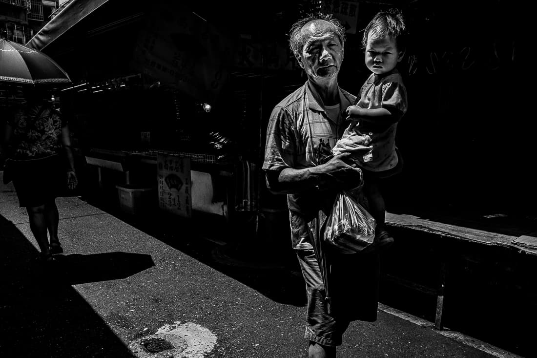 Little kid held by grandfather in Bailan Market