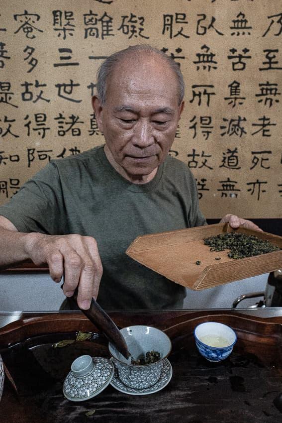 茶則から茶葉を入れる男