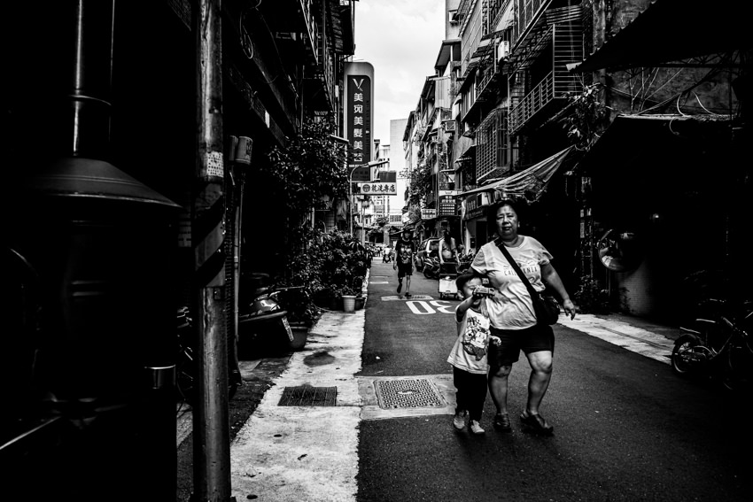 Stout mother and her little son walking lane