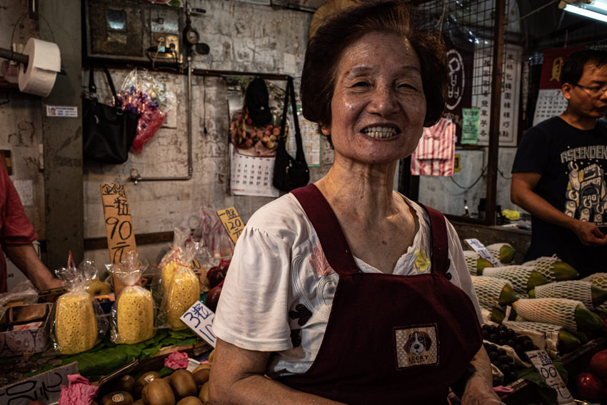 Woman smiling in front of fruits