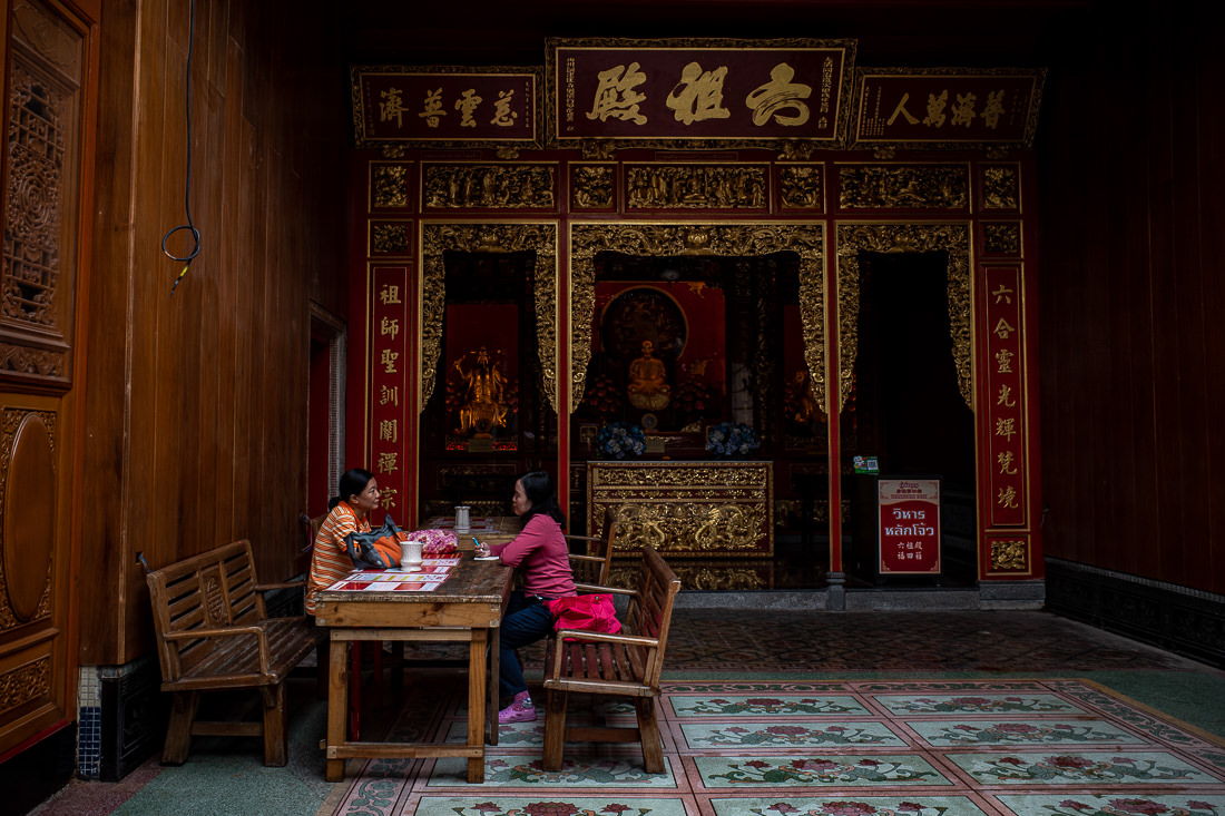 Two women resting in front of an altar