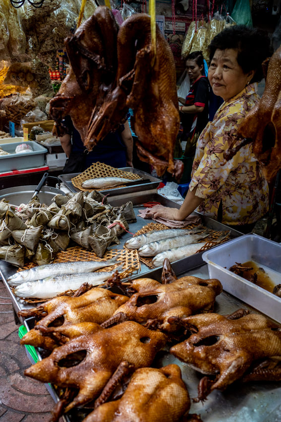 Roasted chickens, fishes, and Zongzi in front of woman