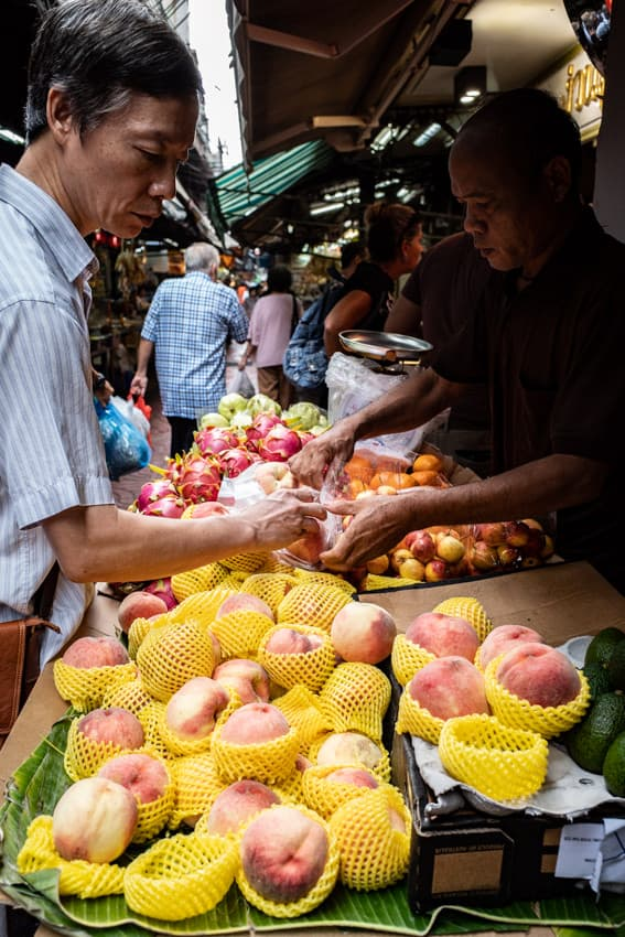 桃を果物店で買い求める男