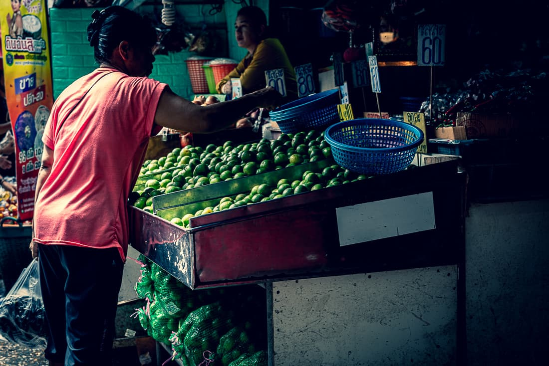 Woman browsing oranges in Khlong Toei Market
