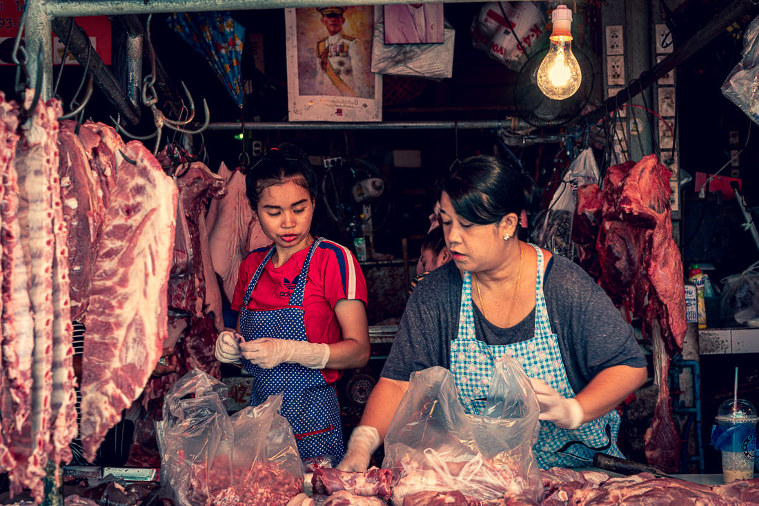 Two woman working together in a butcher in Khlong Toei Market