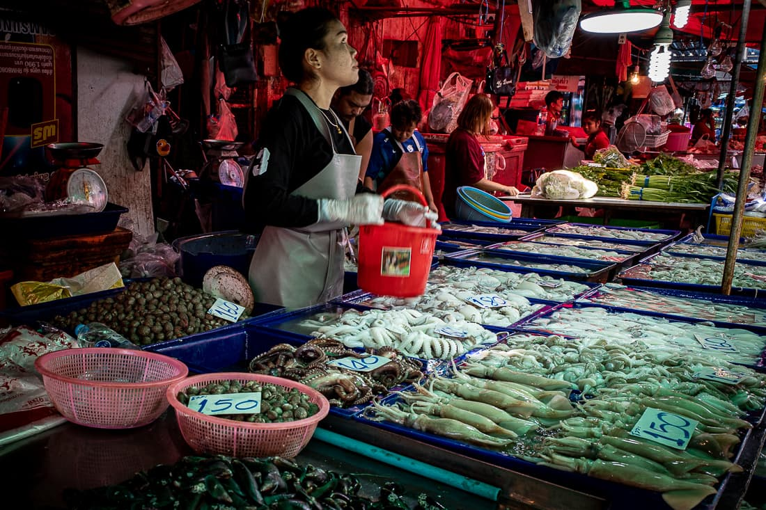 Young woman selling squid, octopus, and shell in Khlong Toei Market