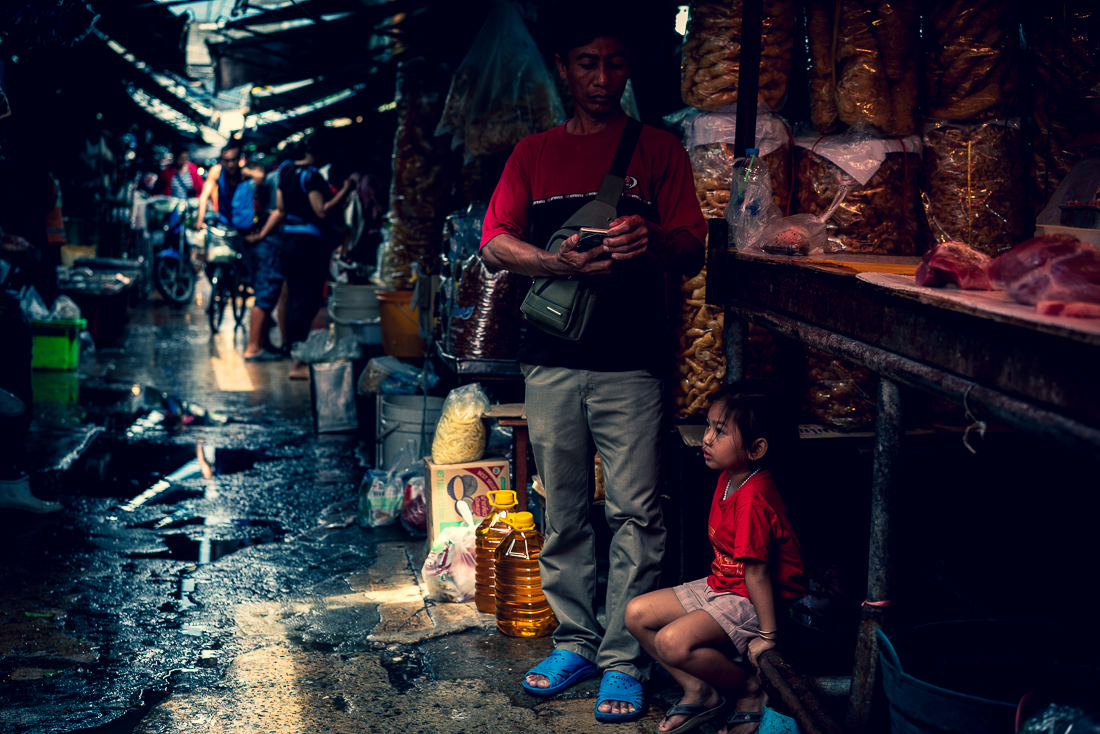 Girl planting herself down in Khlong Toei Market