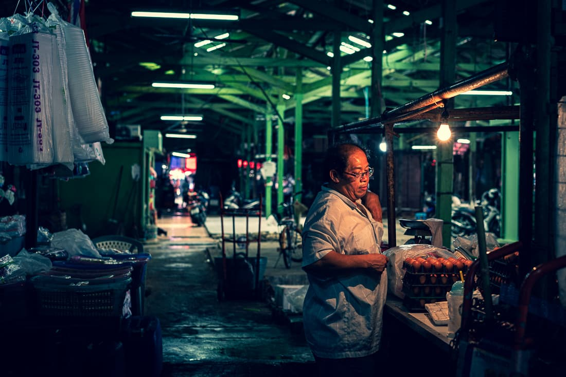 Man standing in a dim passage in Khlong Toei Market in Bangkok. The place seemed to be his shop. A bare bulb was lighted. And some row uncooked eggs were seen on the counter.