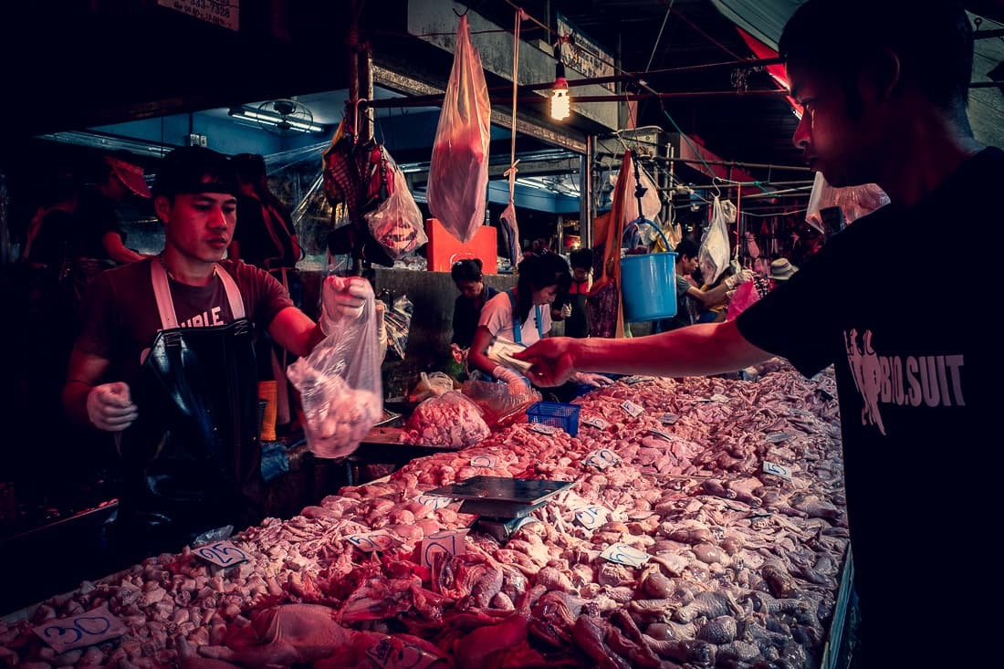Man buying meat in a butcher in Khlong Toei Market