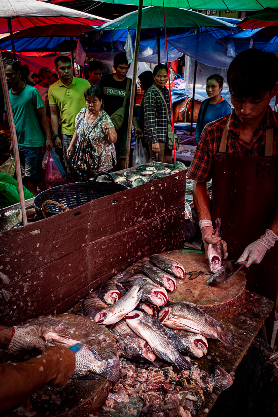 Man cutting fishes in Khlong Toei Market