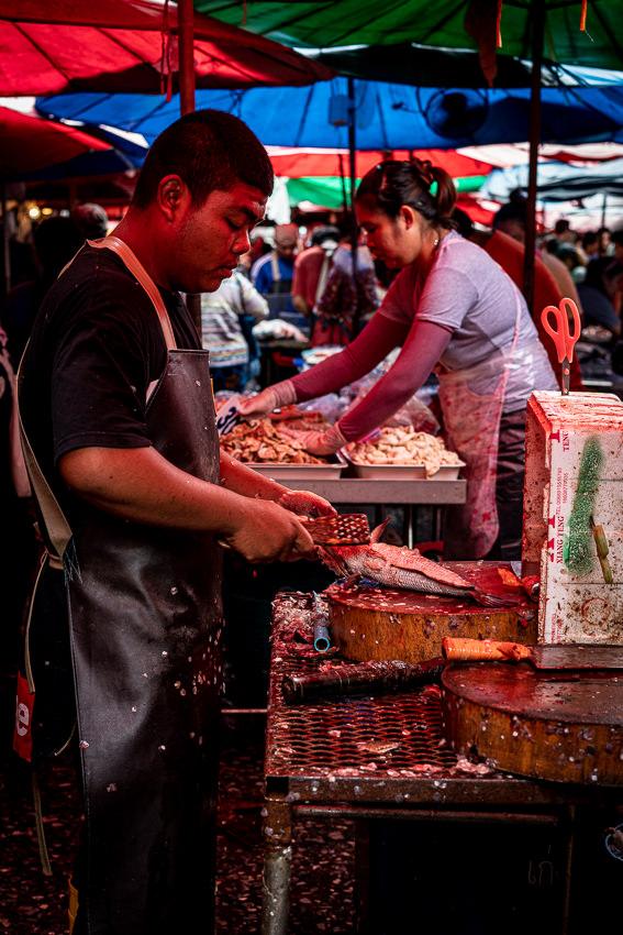 クロントゥーイ市場で魚のウロコを取っていた男