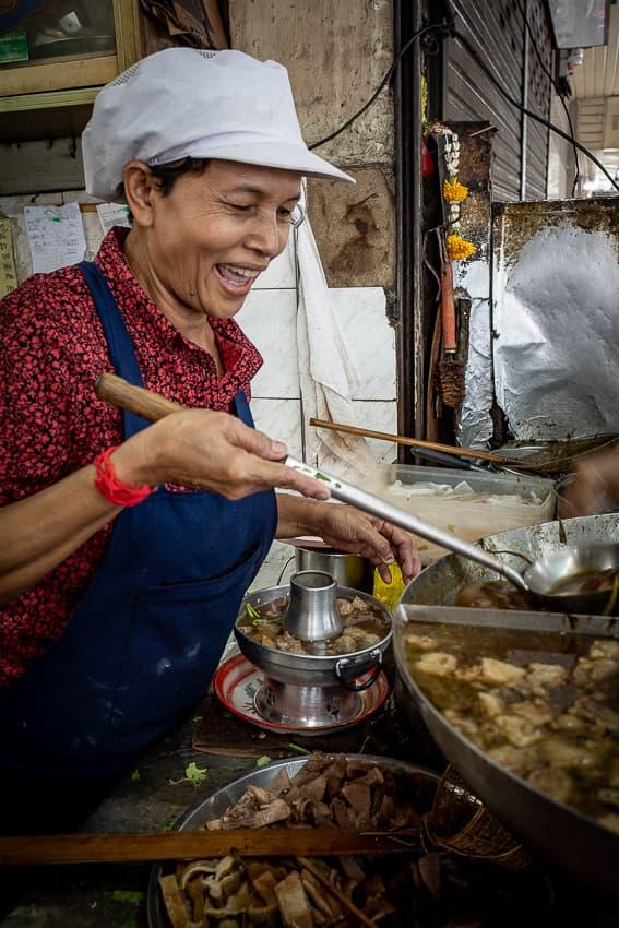 鍋でモツを茹でる女性