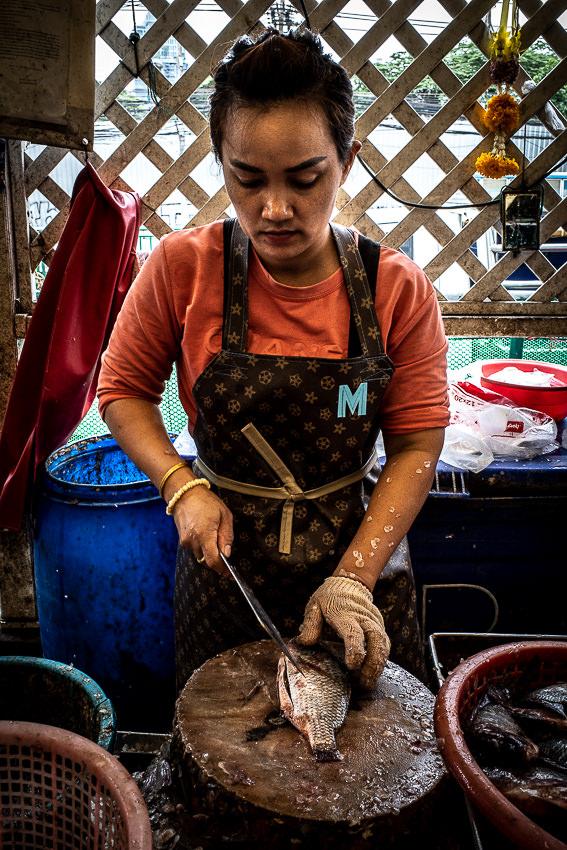 Woman wearing a Louis-Vuitton-like apron in Khlong Toei Market