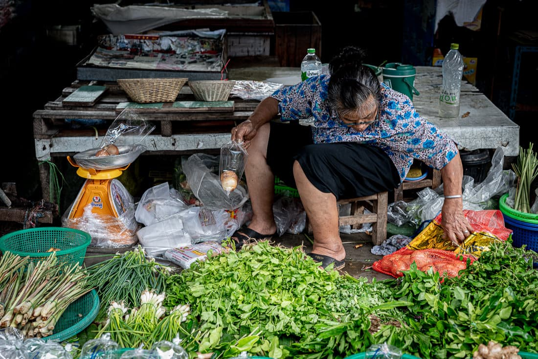 Older woman scouting around in Maeklong Railway Market
