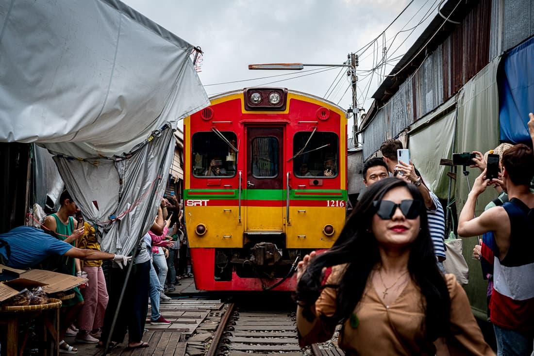 メークロン線路市場に入ってきた列車に色めき立つ観光客