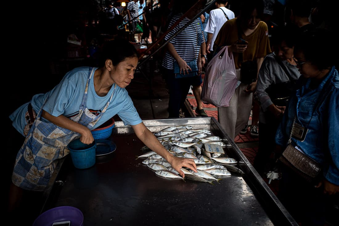 Woman selling fishes in Maeklong Railway Market