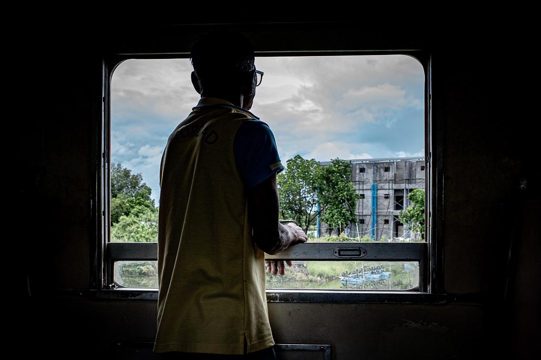 Man gazing out the car window on Maeklong Railway