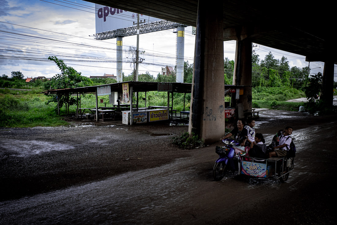 Motorbike running in parallel with Maeklong Railway