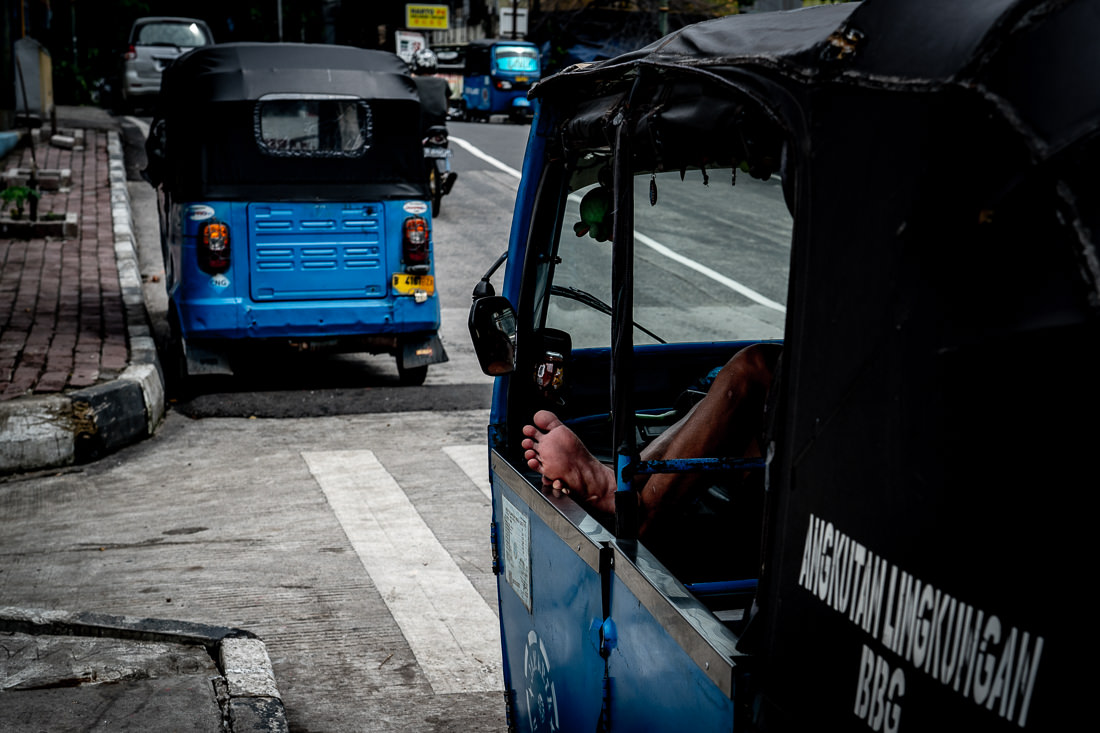Blue three-wheeled taxi called Bajaj in Jakarta