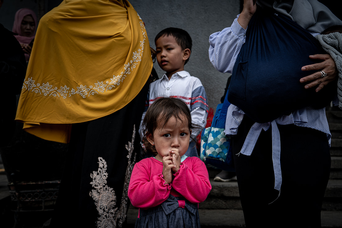 Little girl putting her hands to her mouth in front of Jakarta Kota Station
