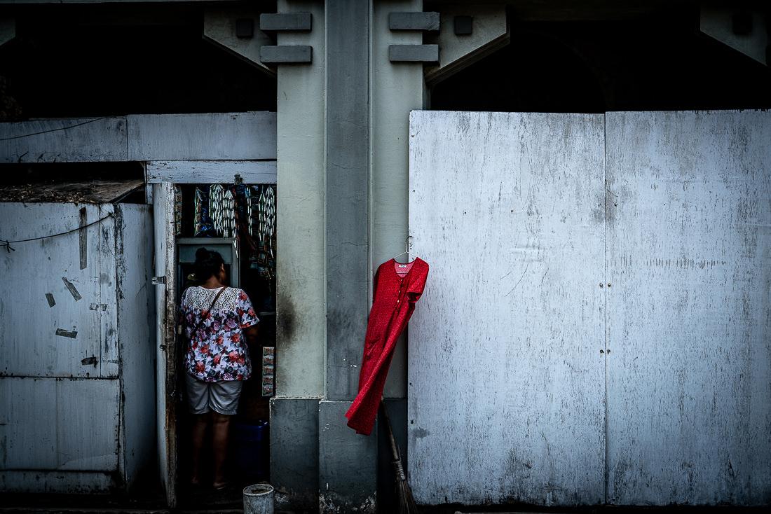 ジャカルタの町角の壁にかかる赤いワンピース