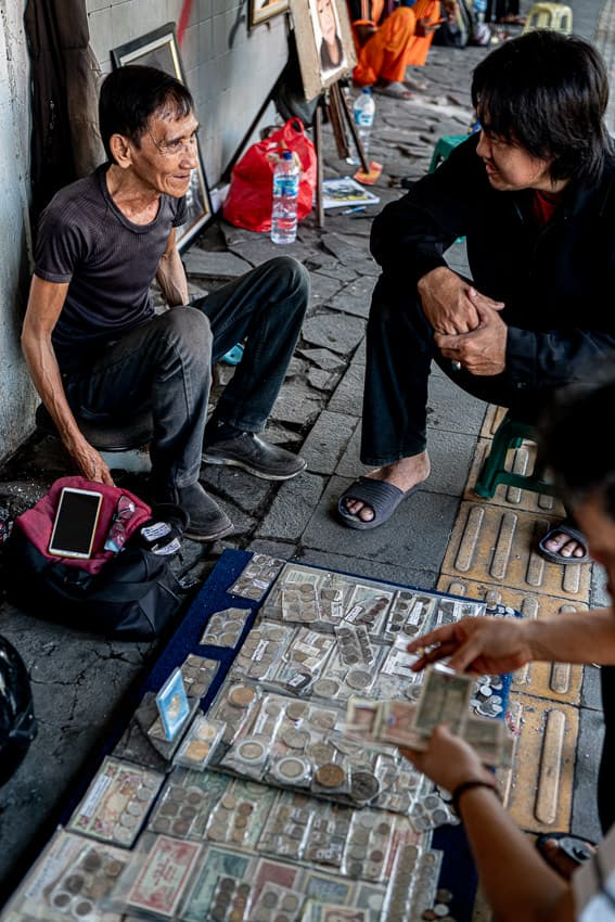 Old coin seller doing business in a street corner in Jakarta