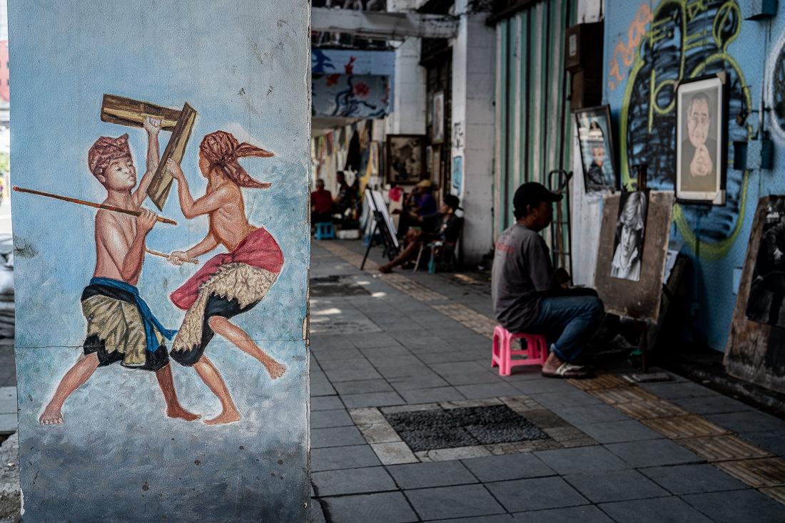 歩道に並ぶ画家と柱にも描かれた絵画