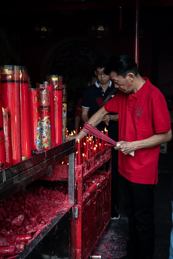 金徳院で燭台を片付ける赤いポロシャツの男