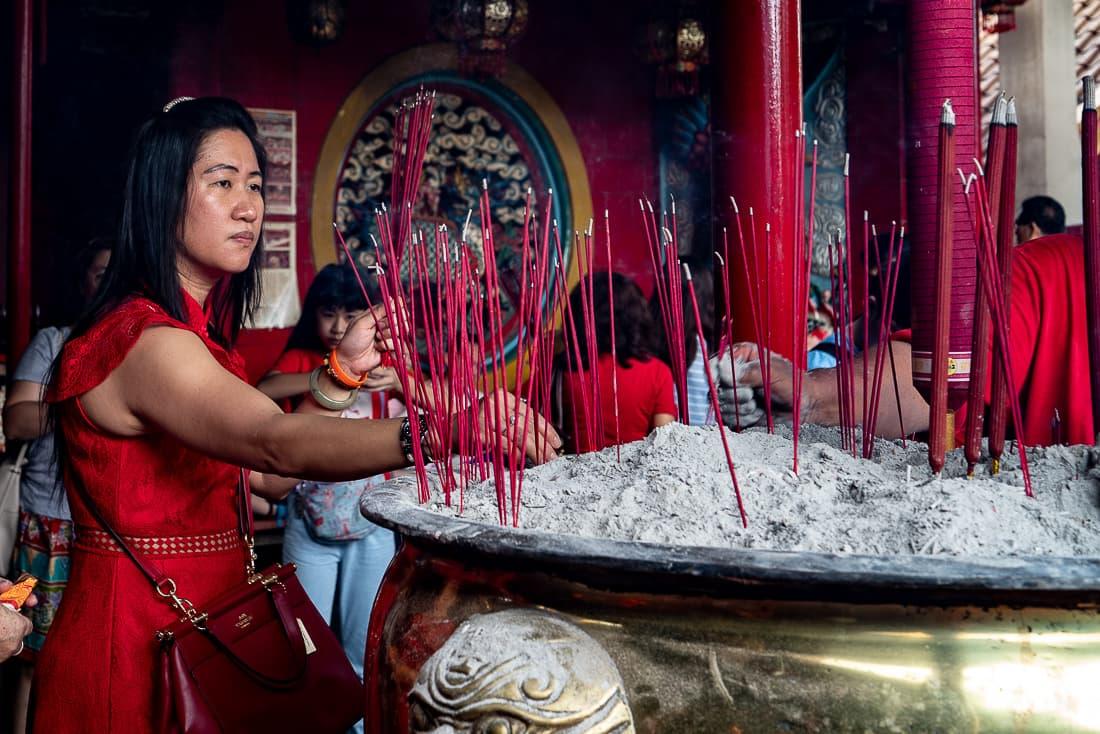 Woman in a red dress sticking red incense sticks in Jin De Yuan