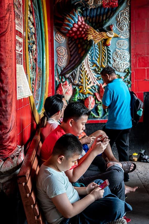 金徳院で携帯ゲームに夢中になっている若者
