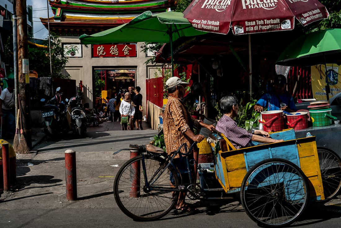 Pedicab called becak parked in front of Jin De Yuan