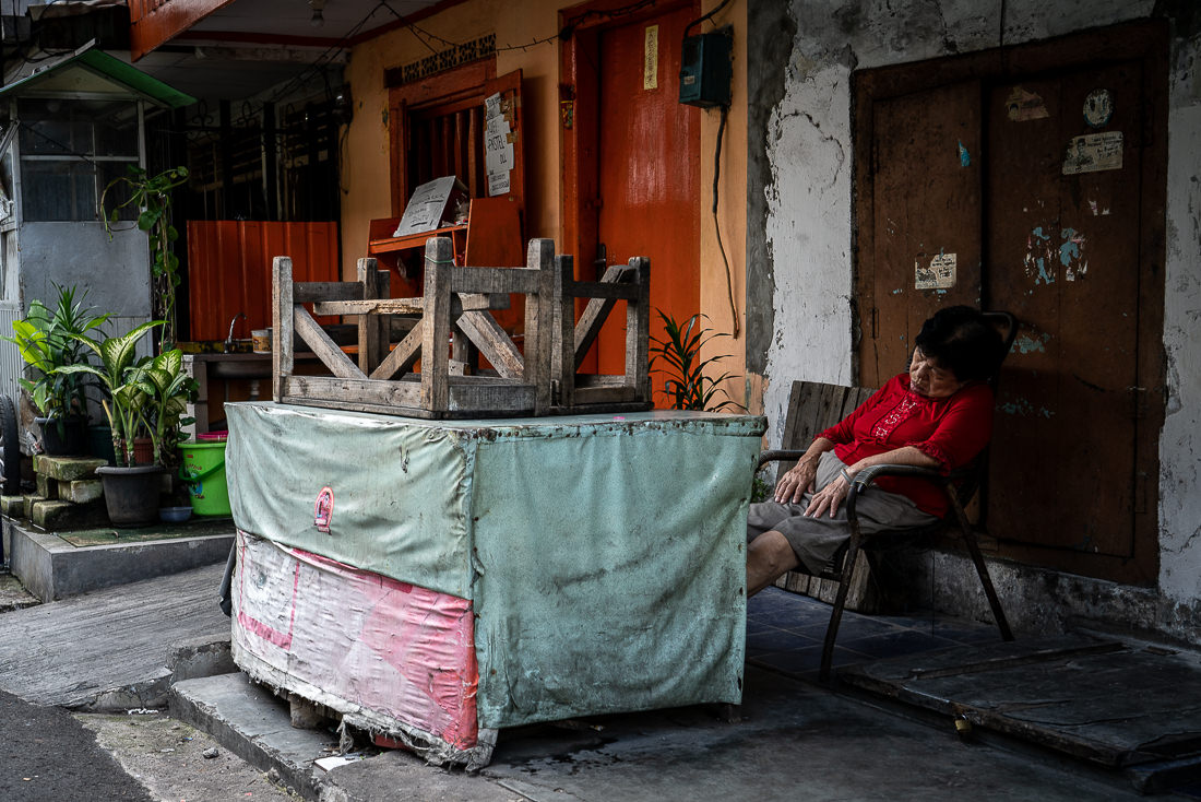 Older woman sleeping soundly in front of a closed shop