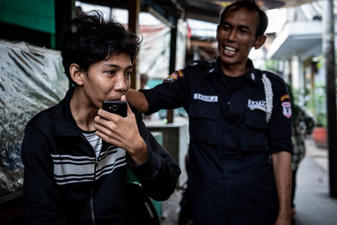 Two men standing talking in the residential area in Jakarta