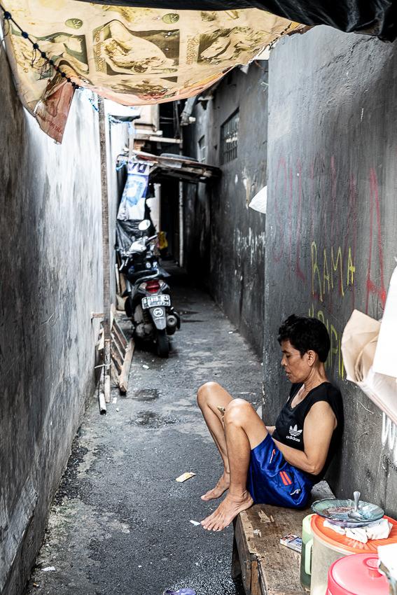 ジャカルタの路地で休む屋台の店主