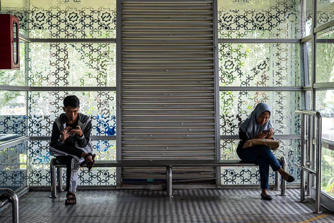 Man and woman sitting on the bench at the bus stop