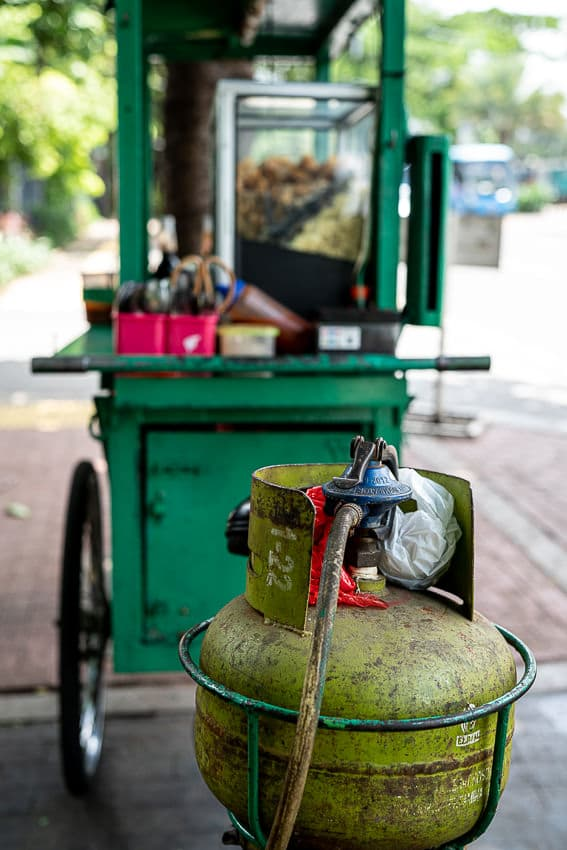 Green gas cylinder next to a food stall
