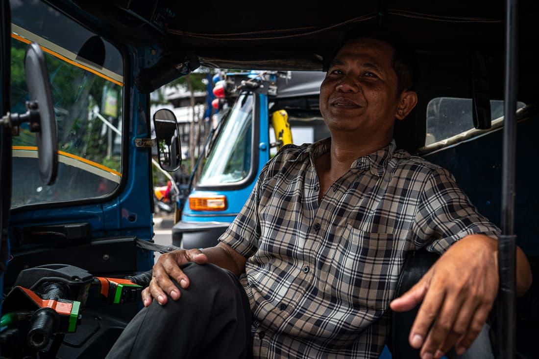 Bajaj driver wearing a checkered shirt