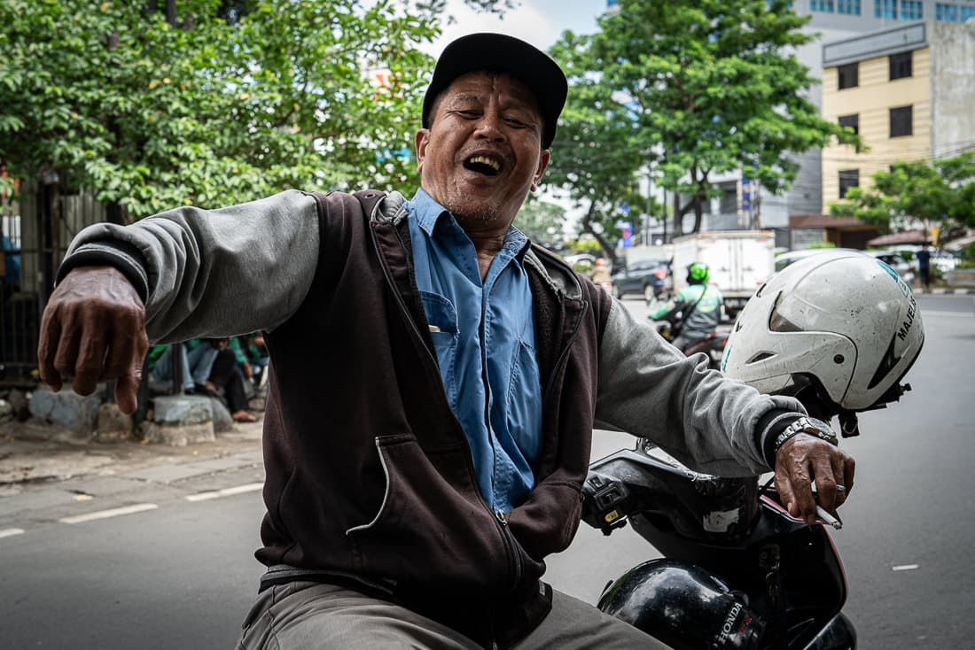 Motorbike taxi driver waiting for customers at an intersection