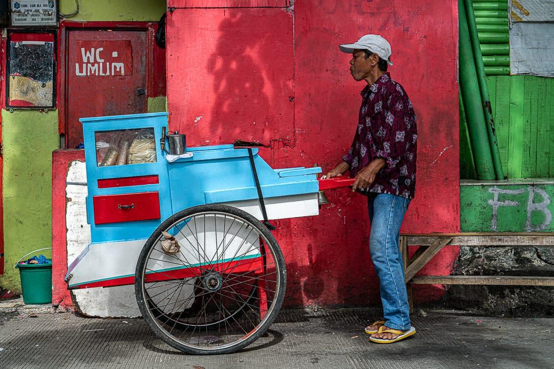 Jakarta peddler pushing a bright stall