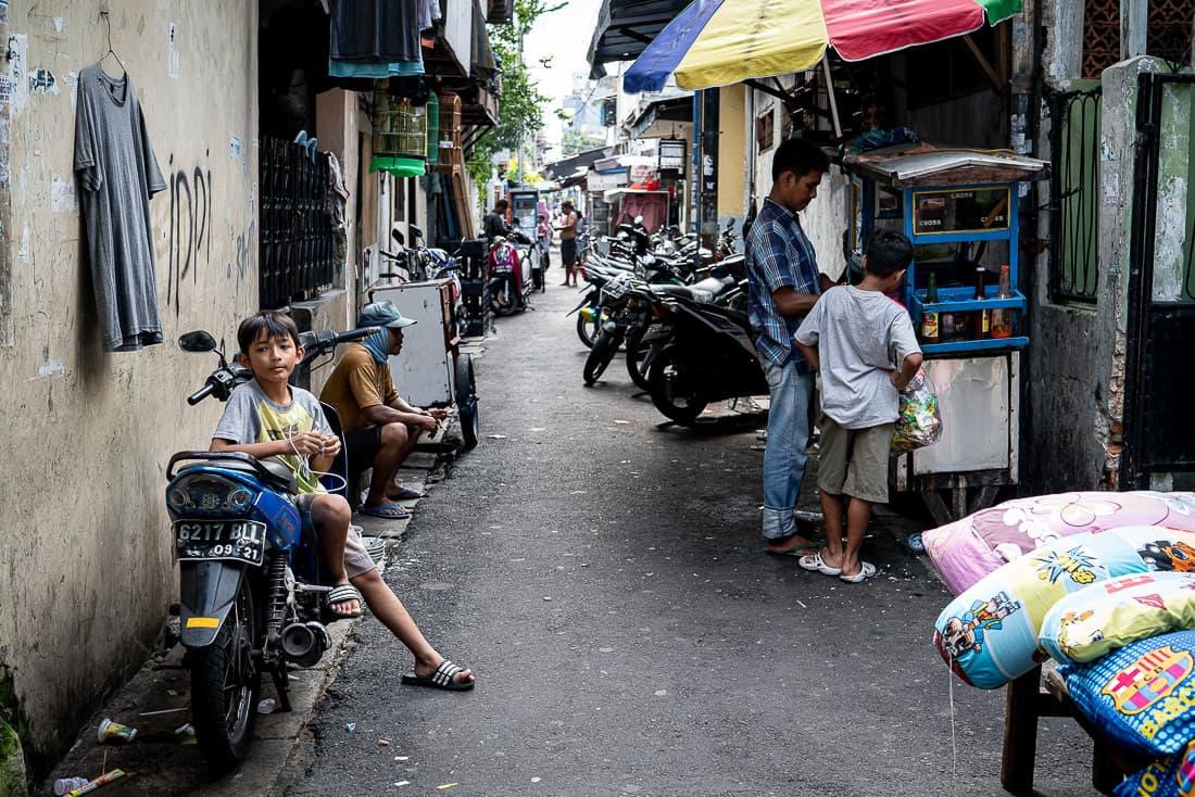 Boy sitting on motorbike instead of bench