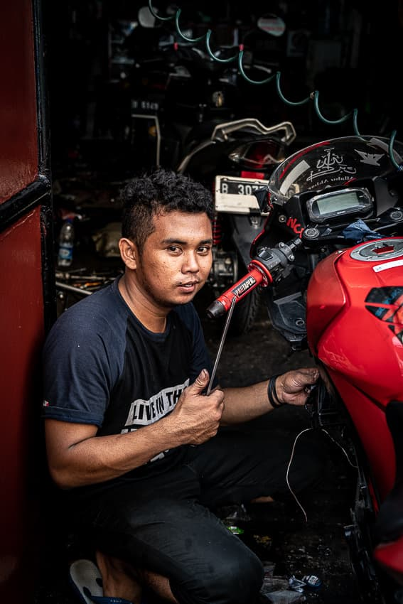 Young man maintaining a red motorbike
