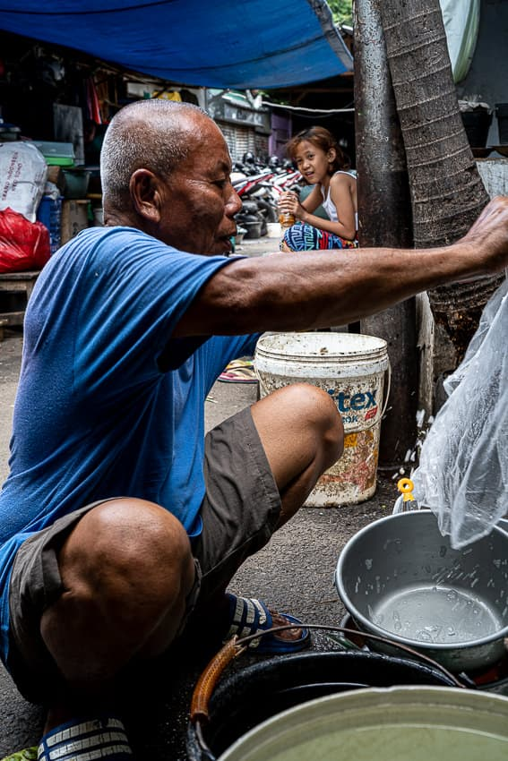 Old man washing up buckets