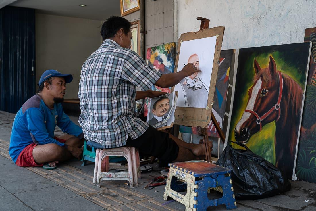 Man painting a portrait in the sidewalk