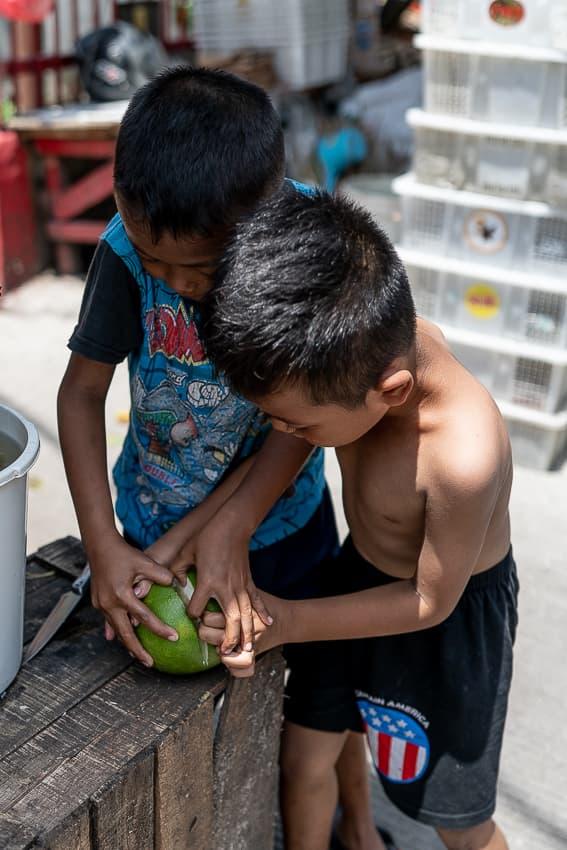 門前で果物を食べようとする男の子